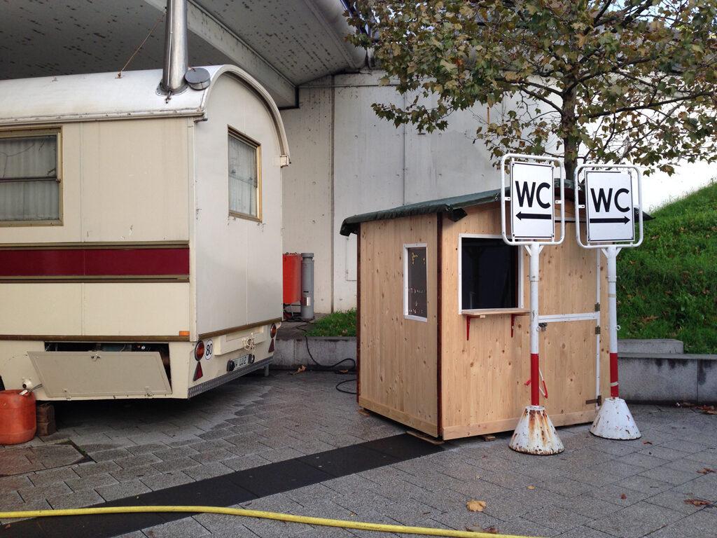 Zwei WC-Tafeln, dessen Pfeile je in die andere Richtung zeigen, stehen vo einem Kassenhäuschen und neben einem Wohnmobil.