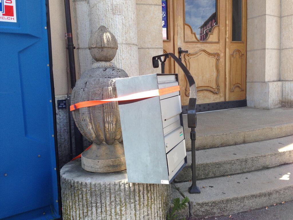 Ein Briefkasten ist vor einem Haus an einen Pfosten angebunden mit einem Spannset.